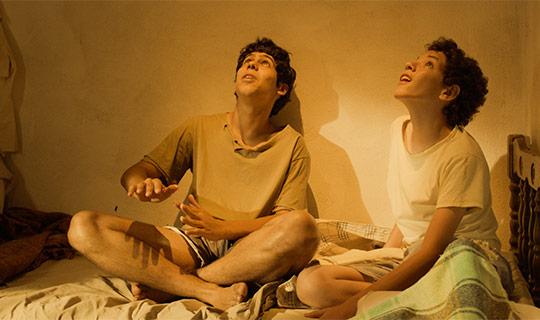 Imagem dois garotos sentados em uma cama