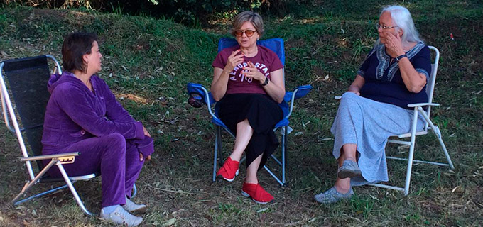 três mulheres sentadas em cadeiras de praia no parque, conversando