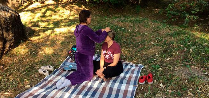 mulher prestando atendimento terapêutico a outra mulher em uma toalha sobre a grama