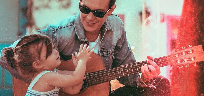 Músico Dan Arruda tocando violão enquanto sua filhinha bate palma ao seu lado
