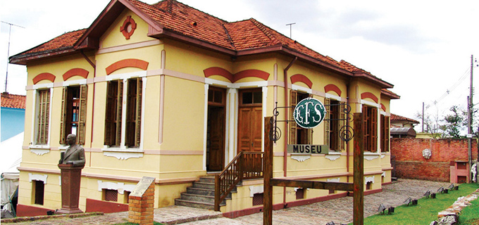 imagem da lateral da casa e placa do Museu da Estrada de Ferro Sorocabana (MEFS)
